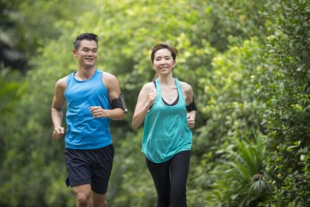 Foto de Athletic Asian man and woman running outdoors. Action and healthy lifestyle concept. - Imagen libre de derechos