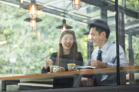 Foto de Asian business man and woman meeting in a coffee shop. - Imagen libre de derechos