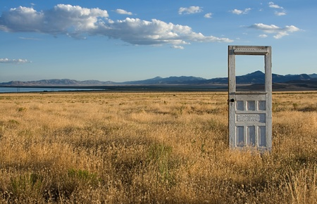 An antique or vintage door standing alone in a grassy feild, with mountains and a bueatiful sky in the background.