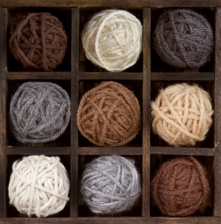 Assorted balls of natural colored yarn in a printers box
