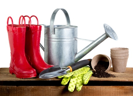 Gardening tools and red rubber boots isolated on a white background