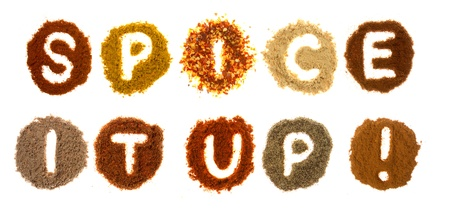 Assorted spices spelling the word spice it up, isolated on a white background