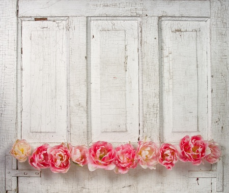 Flowers on a paneled vintage door, (pink tulips or roses like flowers)