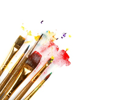 Assorted paint brushes on canvas background with paint splatter on white background