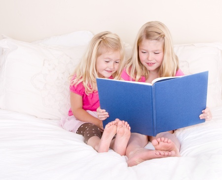 Sisters on bed reading book
