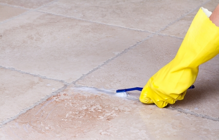 gloved hand cleaning tile grout with toothbrush