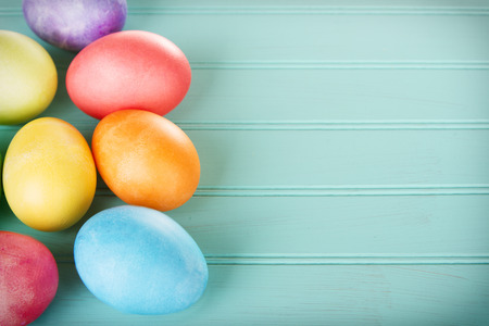 Dyed Easter eggs on a turquoise blue wooden panel
