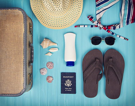 A collection of travel items including suitcase, passport, sandals, sunglasses, swim suit, sunscreen and straw hat on turquoise background