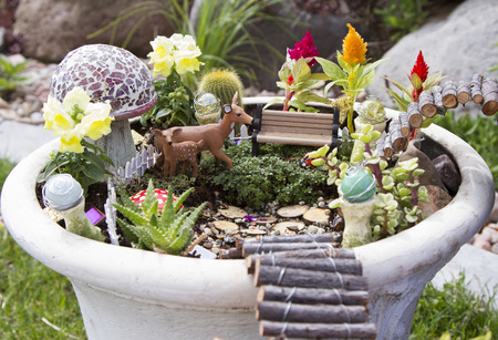 Fairy Garden With Deer Gazing Balls And Mushrooms In A Flower Pot
