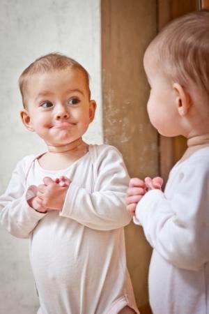 Photo pour Baby standing against the mirror  - image libre de droit