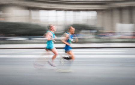 Blurry scene of unknown running men competed on road in fast motion.