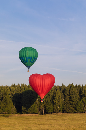 Colorful hot-air balloon flying over the forest, postcard concept