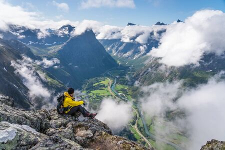 Photo for Young man traveller sitting and looking to mountains in Romsdalseggen hiking trail, Norway, Scandinavia, Europe - Royalty Free Image