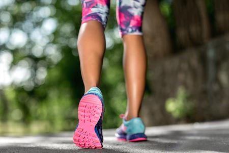 Foto de Woman fitness sunrise jog workout welness concept. Runner feet running on road closeup on shoe. - Imagen libre de derechos