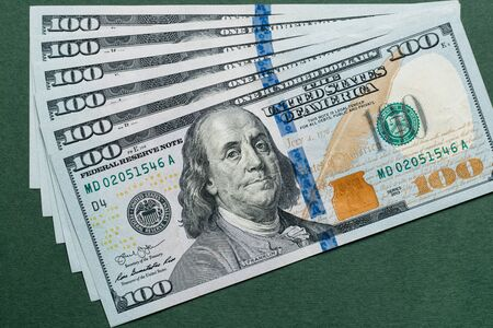 Photo pour Stack of one hundred american dollars bills over green background. - image libre de droit