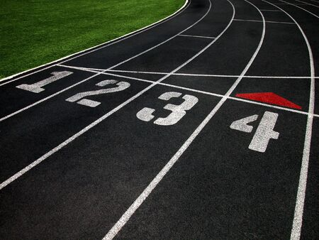 The Black Surface of a Cushioned Running Track with Marked Lanes