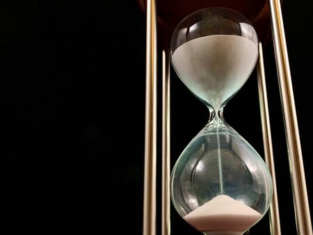 Photo pour Hourglass on a stand, black background. Glass hourglass in the case. Glass time meter. Concept: time is running out, time management, time resource - image libre de droit