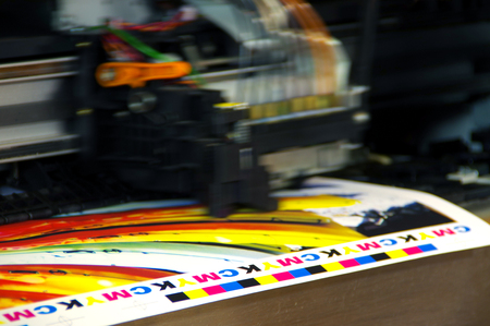 Photo pour Inkjet printer plotter head moving over CMYK mark on white paper. Large digital printing machine. - image libre de droit