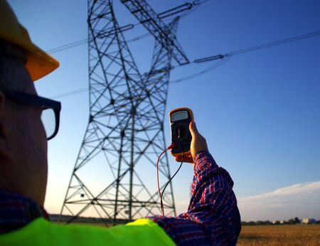 Foto für Engineer with gauge during power line infrastructure inspection. Electrician at survey. Measurement of energy network. - Lizenzfreies Bild