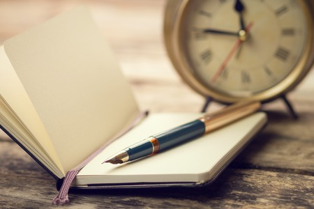 Open small notebook with fountain pen and old-fashioned alarm clock behind. Warm color toned vintage image