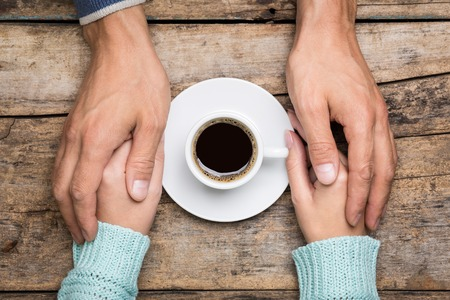 Man holds woman's hand near a cup of coffee top view image on wooden backdrop. Friendship coffee background