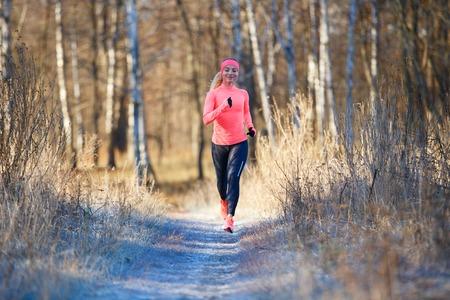 Foto de Young girl running in the park in early winter - Imagen libre de derechos