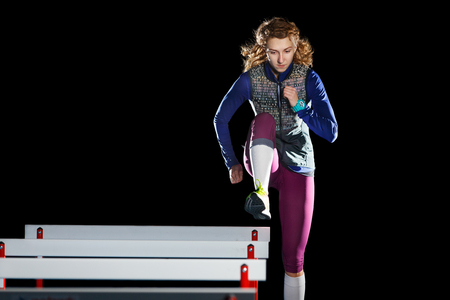 Foto per Young female athlete training running with hurdles - Immagine Royalty Free