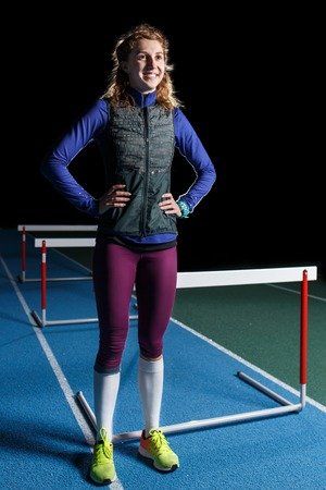 Foto per Young smiling female athlete standing near hurdle - Immagine Royalty Free
