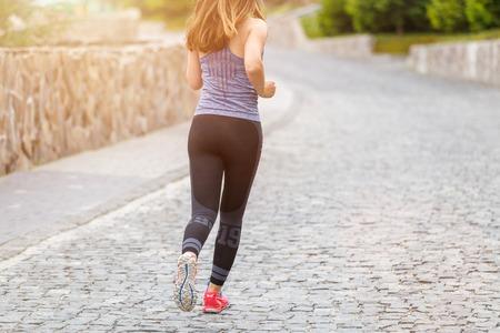 Foto de Back view of running woman on cobbled road with copy space aside - Imagen libre de derechos