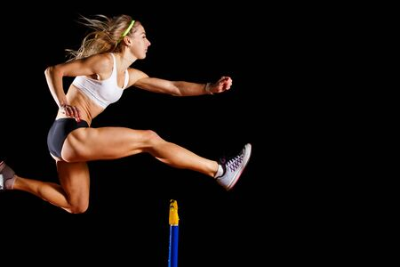 Photo for Muscular sportswoman jumping over hurdle on sprint race isolated on black background - Royalty Free Image