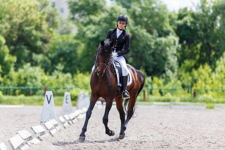 Photo pour Young woman riding horse on dressage advanced test - image libre de droit