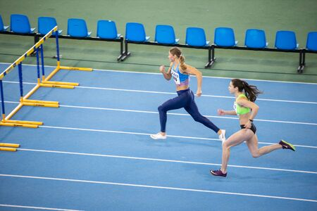 Photo for SUMY, UKRAINE - FEBRUARY 22, 2020: champion Anna Plotitsyna on 60m hurdles sprint at Ukrainian indoor track and field championship 2020. - Royalty Free Image