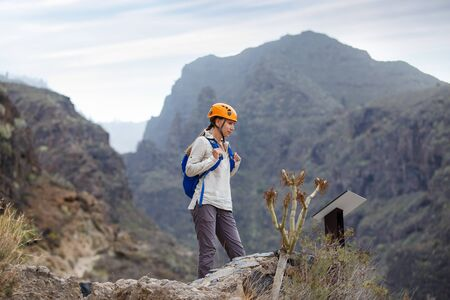 Photo for Young woman with backpack enjoying mountains on trekking trip in volcanic ravine on Tenerife, Spain - Royalty Free Image
