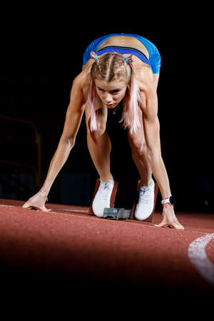 Foto per Young sprinter girl on the lane starting her run. - Immagine Royalty Free