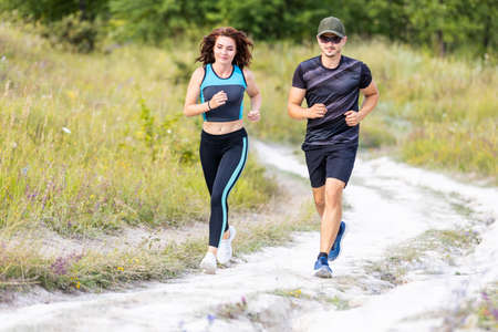 Photo pour Sporty man and woman run on the country road - image libre de droit