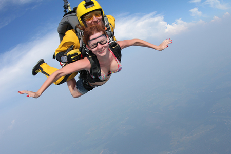 Photo pour Skydiving. Girl and tandem-master are flying in the sky. - image libre de droit