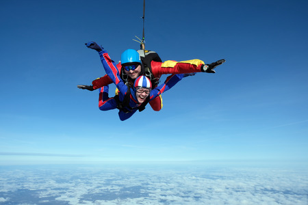 Photo pour Skydiving. Man and woman are flying in the sky together. - image libre de droit