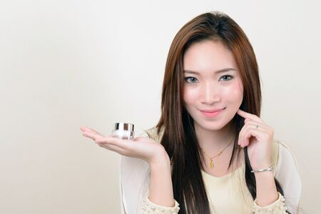 portrait of beautiful  smiling healthy asian woman is holding cosmetic container