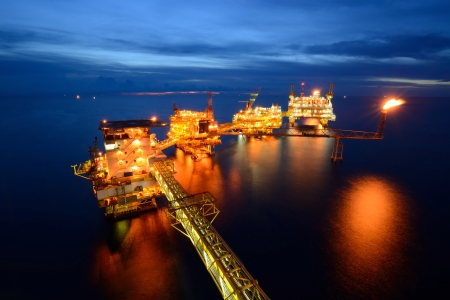 The  large offshore oil rig at night with twilight background