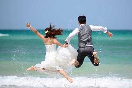 Foto de happy just married young couple celebrating and have fun at beautiful beach - Imagen libre de derechos