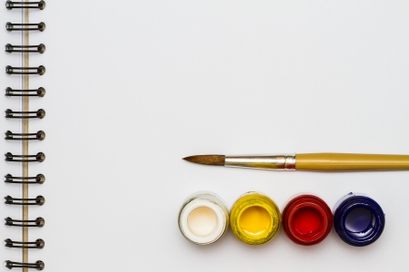 Paint brushes with opened paint buckets on drawing book