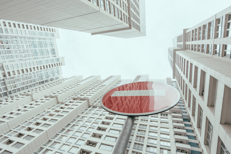 View from bottom of modern contemporary white skyscraper apartment building with regular windows and balconies on a bright day with a red stop road sign reflecting the building, Moscow, Russia