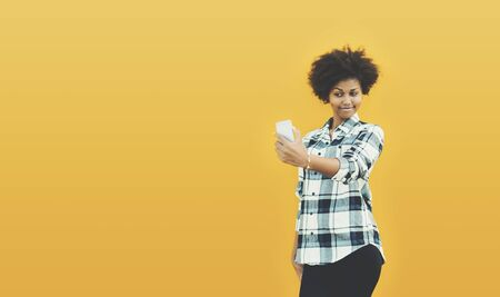Charming curly smiling Brazilian girl is making selfie on smart phone while standing in front of clear yellow background with copy space for your advertising text message or promotional content