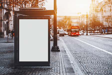 Photo pour White empty information mock-up on city bus stop, blank vertical billboard near paved road with red touristic bus, clear placeholder frame in urban settings with copy space for text or advertising - image libre de droit