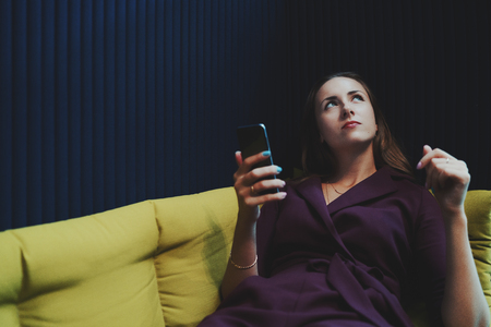 Charming caucasian business lady in purple suit with blue eyes is reflectively looking up while laying on green sofa in office lounge zone and having online chat via her smart phone