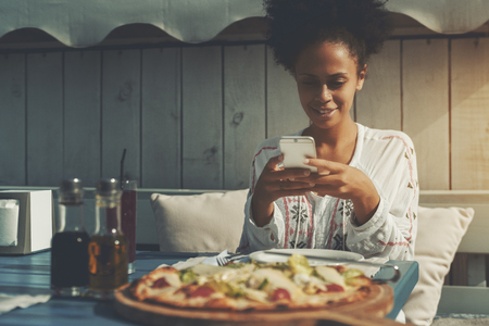 Charming young black female is taking picture of her freshly baked Caesar pizza using rear camera of smartphone; cute mixed woman is photographing recently brought food in street restaurant in evening