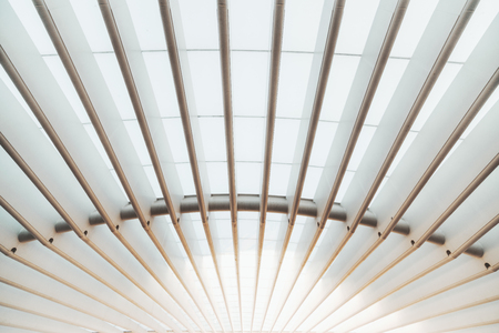Photo pour A wide-angle view of a white outdoor roof construction of a modern building made of parallel thick hollow iron girders and translucent covering to pass and scatter the sunlight - image libre de droit