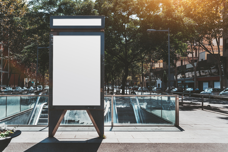 Photo pour Mockup of an outdooradvert blank vertical poster near an underground entrance; template of a vertical information banner on the street near a metro; an ad empty white placeholder in urban settings - image libre de droit