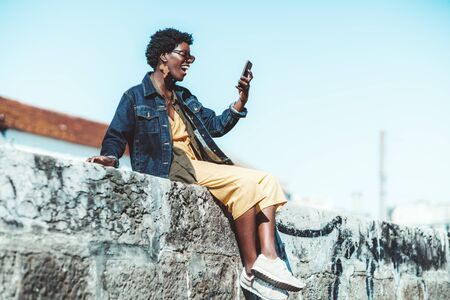 Foto de A happy laughing African female in a denim jacket is having a video call via her smartphone with her friend while sitting outdoors on a stone wall on a sunny day, with a copy space area on the right - Imagen libre de derechos