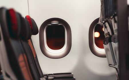 A dark aircraft interior: the row of modern empty leather seats with armrests down, shallow depth of field, selective focus on the the window with a night lights outside